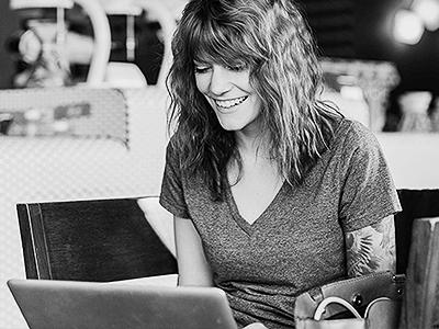 Image of woman smiling at laptop
